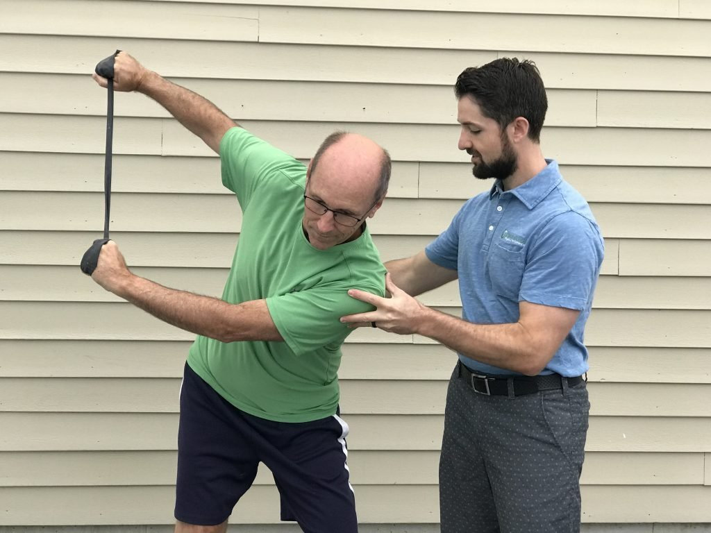Physical therapist helping a golfer with rotation using a resistance band