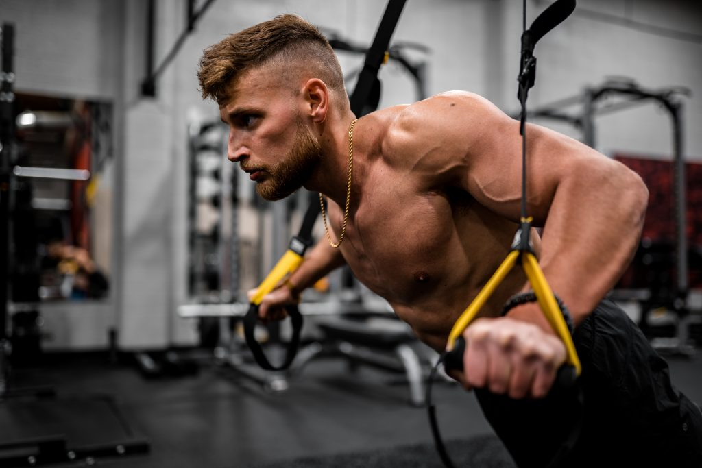 Fit guy using TRX for core work