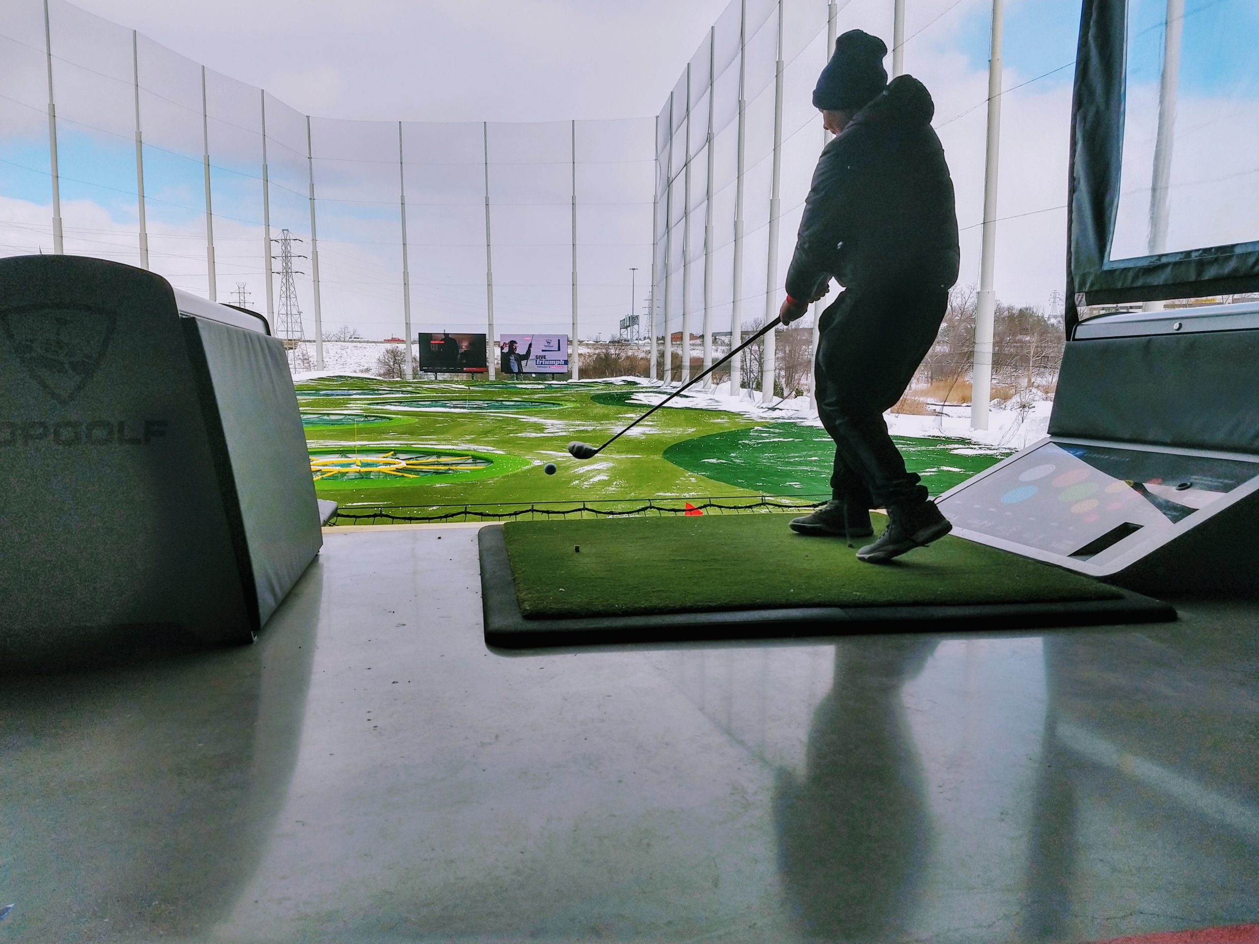 Golfer at driving range wearing winter clothes