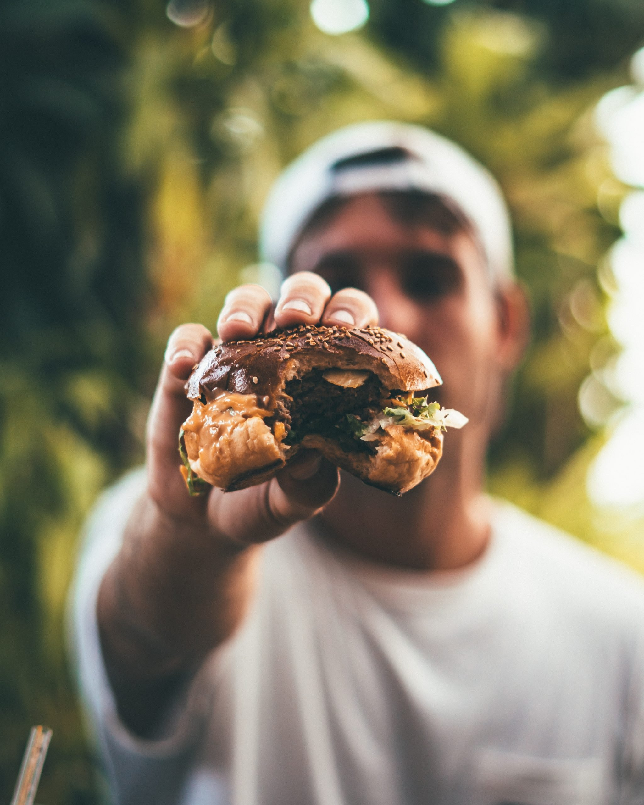 Guy holding a cheeseburger with a bite taken out