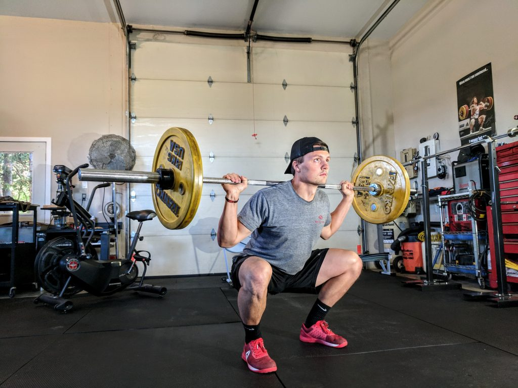 Guy squatting with a barbell