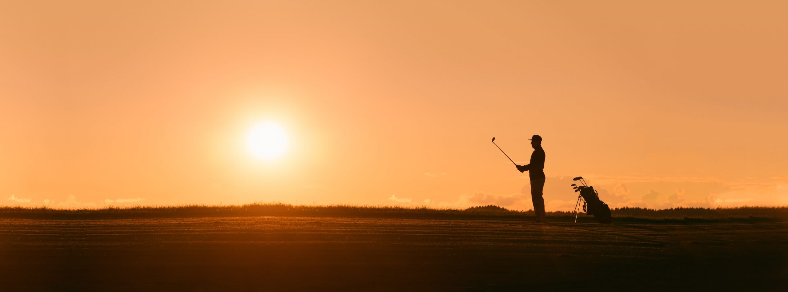 Silouhette of a golfer in the sunset