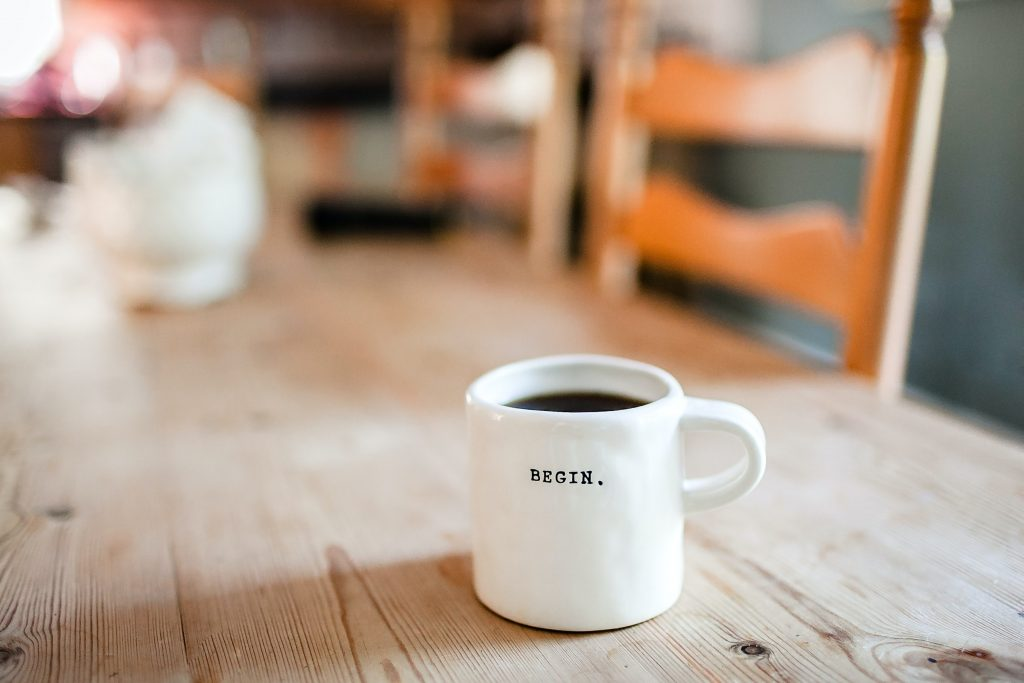 """A full cup of coffee on a table and the mug reads """"begin"""""""