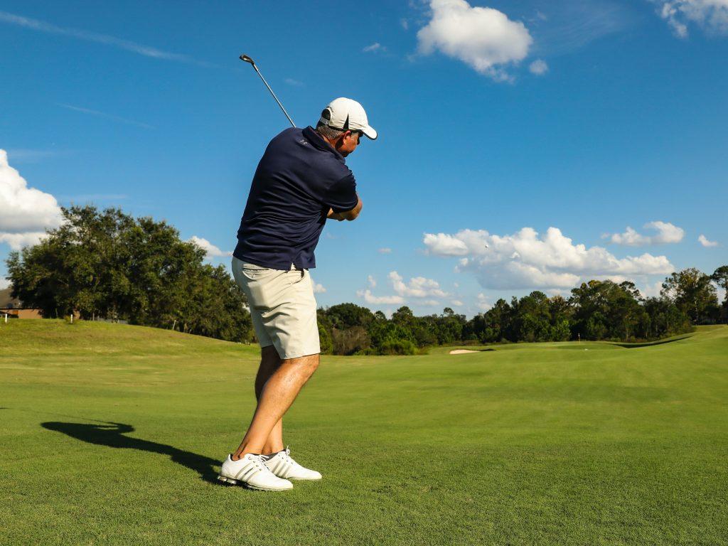 Guy Swinging Golf Club On Fairway