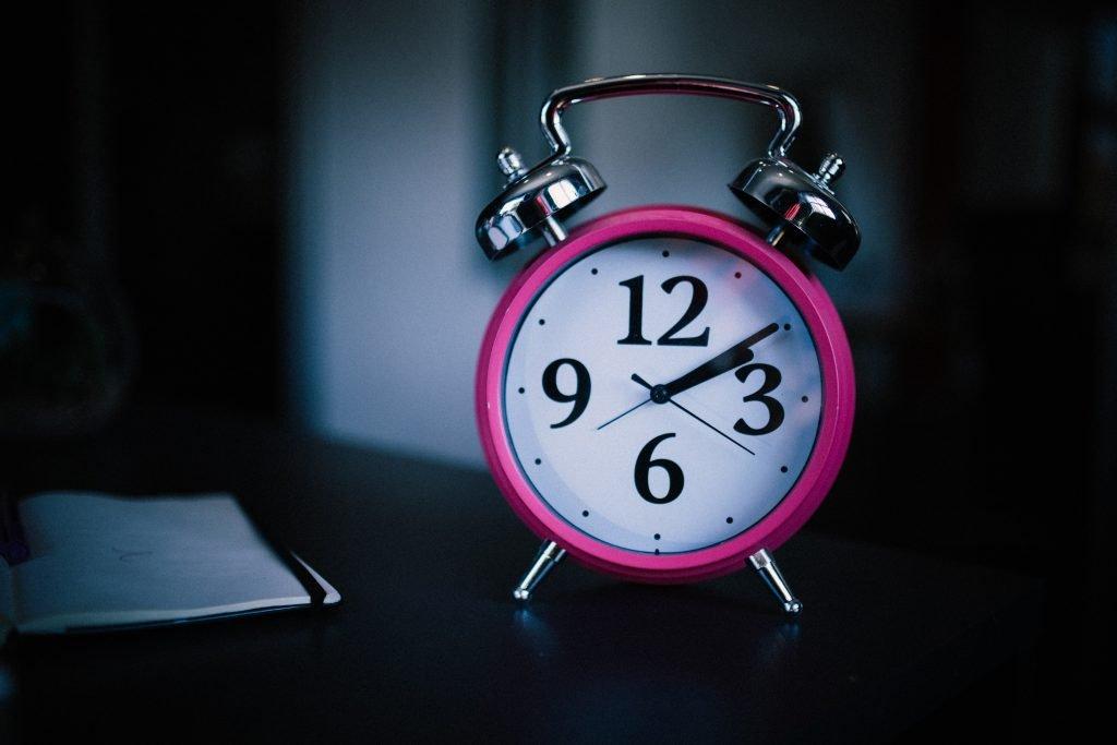 Pink alarm clock on table