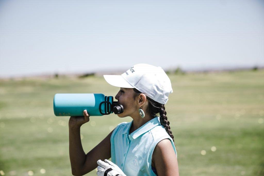Female golfer drinking from water bottle
