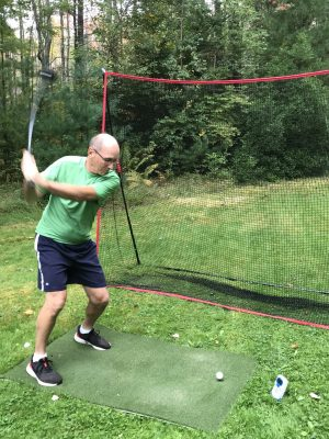 Golfer hitting ball into net